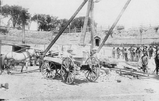 Quarry workers in a Howard quarry using a derrick.