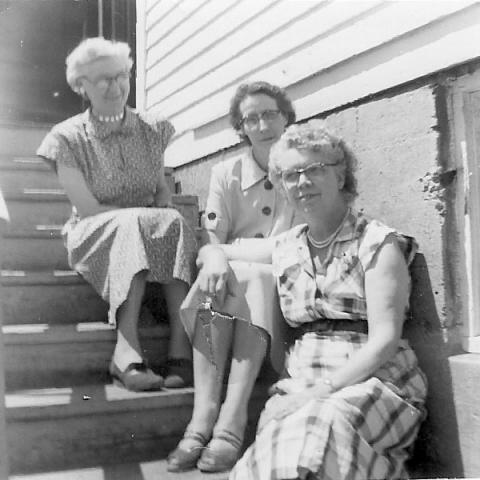 Three West Lakeside School teachers. They are sitting on the back steps of the school. Mrs. Jingle, Mrs. Knudson, and Mrs. Ruth Kline.